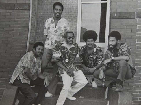 This throwback photo is of late A Nubian Notion, Inc. Founder Malik A. Abdal-Khallaq (center) and friends outside of his first Boston based business, a barbershop in Roxbury.